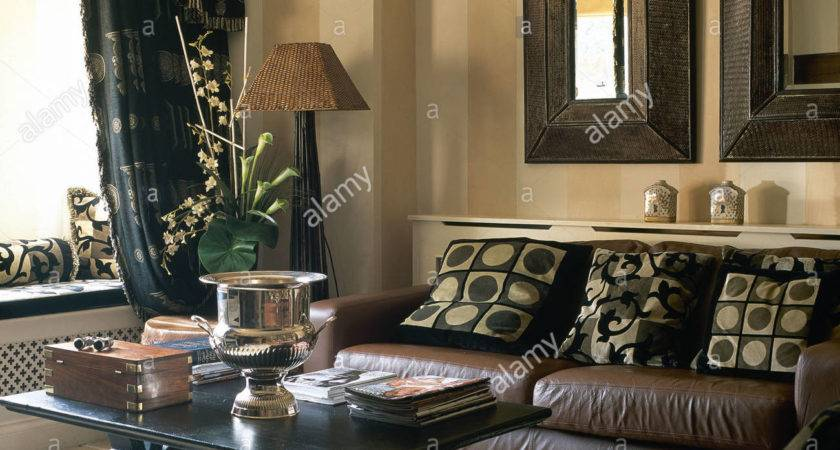 Heavy Wood Framed Mirrors Above Brown Leather Sofa